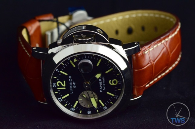 Unboxing Review: Panerai Luminor GMT 44mm [PAM00088] Luminor sitting on its side in low light with the lume glowing slightly