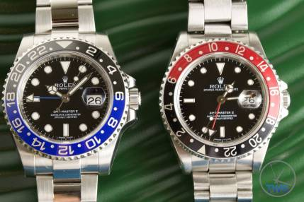 The Rolex 'Batman' GMT Master II [116710BLNR] on the left and the 'Coke' GMT Master II on the right. Both are sat on a green Rolex box.