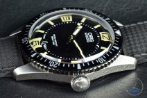 Oris Divers Sixty-Five closeup sitting on black leather with its crown in view [01 733 7707 4064-07 4 20 18]