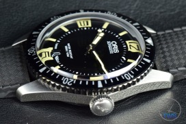 OrisDivers Sixty-Five closeup sitting on black leather with its crown in view [01 733 7707 4064-07 4 20 18]