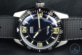 Oris Divers Sixty-Five laying on its side on a black leather surface [01 733 7707 4064-07 4 20 18]