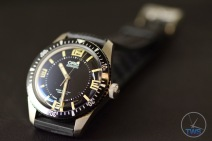 Oris Divers Sixty-Five Laying back on its strap at an angle on black leather with the clasp going out of focus in the background [01 733 7707 4064-07 4 20 18]